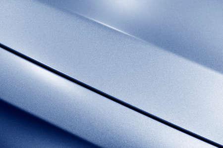 specular: Surface of blue sport sedan car metal hood, part of vehicle bodywork, steel gradient line pattern, selective focus