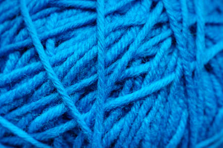 skein: Woolen yarn ball, skein of tangled blue sewing threads, selective focus