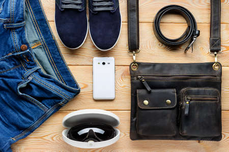 suede belt: Young mens accessories in casual style, fashion industry, bag, jeans, sneakers, sunglasses, belt, mobile phone on brushed wood background, clothes and shoes for spring or summer season Stock Photo
