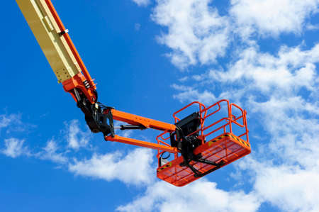 hydraulic lift: Hydraulic lift platform with bucket of construction vehicle painted in orange and beige colors with white clouds and blue sky on background