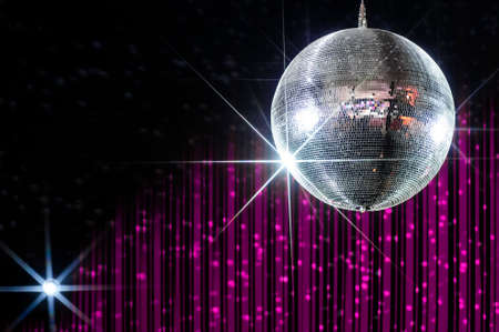 Party disco ball with stars in nightclub with striped pink and black walls lit by spotlight, nightlife entertainment industry Standard-Bild