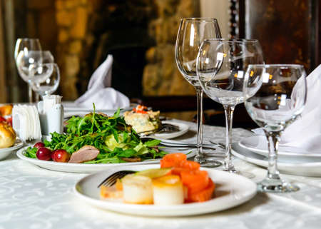 Served for holiday banquet restaurant table with dishes, snack, cutlery, wine and water glasses, european food Stock Photo