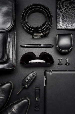 Man accessories in business style, briefcase, gadgets, shoes, clothes and other luxury businessman attributes on leather black background, fashion industry, top view