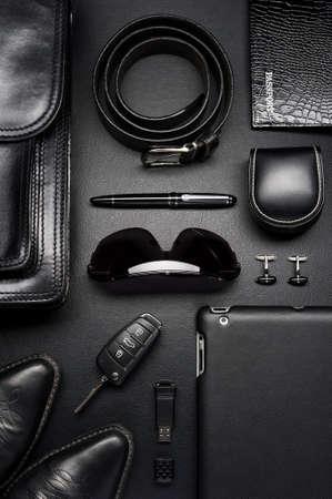 Toebehoren van de mens in zakelijke stijl, koffer, gadgets, schoenen, kleding en andere luxe zaken attributen op lederen zwarte achtergrond, mode-industrie, bovenaanzicht Stockfoto