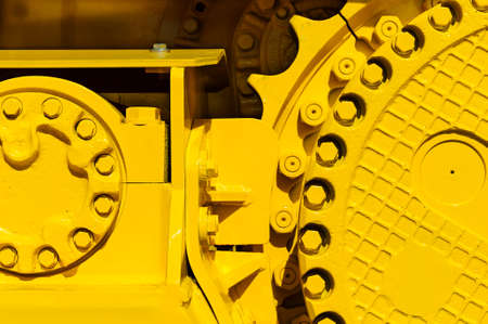 Track drive gear, bulldozer sprocket mechanism, large construction machine with bolts and yellow paint coating, heavy industry, detail