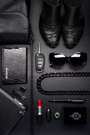 woman bag: Woman accessories in business style, red lipstick, gadgets, shoes, jewelry, car key, bag, sunglasses and other luxury businesswooman attributes on leather black background, fashion industry, top view Stock Photo