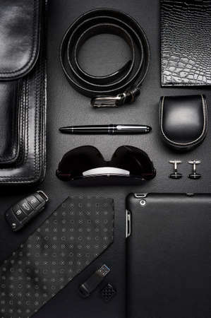 Man accessories in business style, silk tie, gadgets, briefcase, clothes and other luxury businessman attributes on leather black background, fashion industry, top view