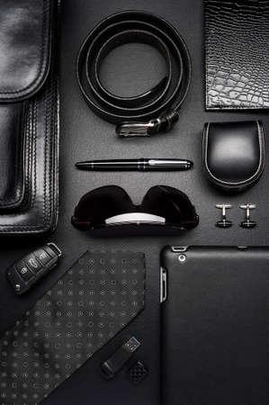 Man akcesoria w stylu biznesowym, krawat jedwabiu, gadżety, aktówka, ubrania i inne luksusowe atrybuty biznesmen na skórzane czarne tło, przemysł mody, widok z góry Zdjęcie Seryjne