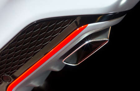 Chrome exhaust pipe of powerful sport car with white bodywork, orange and grey steel and plastic details Stock Photo