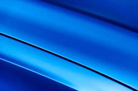 Surface of blue sport sedan car metal hood, part of vehicle bodywork, steel gradient line pattern, selective focus