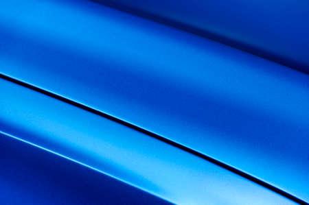Surface of blue sport sedan car metal hood, part of vehicle bodywork, steel gradient line pattern, selective focus