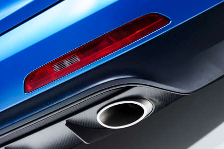 the silencer: Chrome exhaust pipe of powerful racing car with blue bodywork, grey plastic bumper and red back light