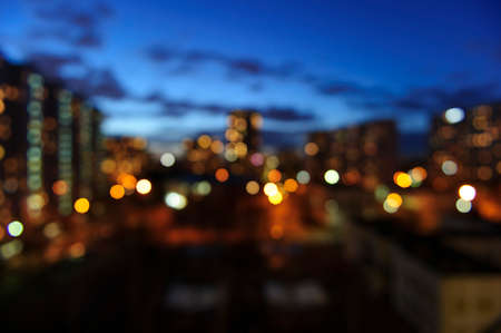Blurred summer evening city buildings lights, window view background Stock Photo