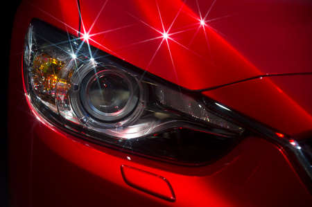Headlight and hood of powerful sports red car with stars on bodywork, isolated on black