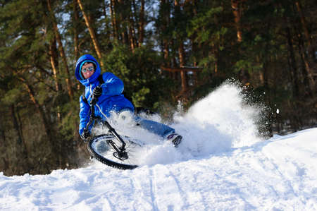 snowbanks: Cyclist riding bike, extreme winter cycling near snowbanks of snowy mountain slope, cross country biking near forest in cool sunny day Stock Photo