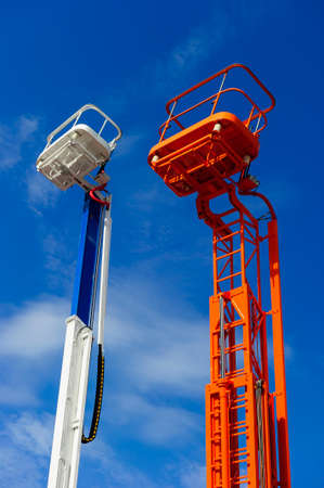 Lift platform with bucket and cherry picker aerial work platforms, construction hydraulic telescopic cranes of orange and white colors, heavy industry, blue sky on background Stock Photo