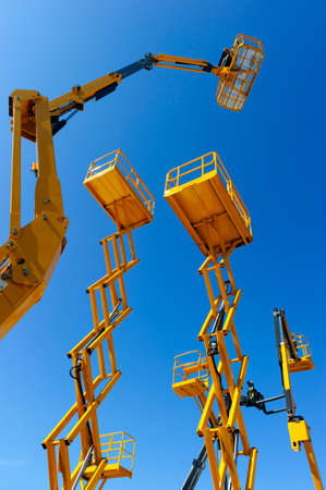 Scissor lift platform, cherry picker, aerial platform with bucket, articulating boom and other yellow construction cranes and machines, heavy industry, blue sky on background, bottom view Standard-Bild