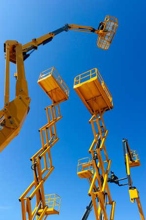 Scherenhubbühne, Kirschpflücker, Hubarbeitsbühne mit Eimer, Gelenkausleger und andere gelbe Baukräne und Maschinen, Schwerindustrie, blauer Himmel auf Hintergrund, Unteransicht