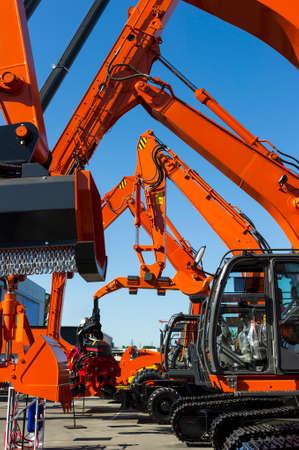 cargador frontal: Bulldozer, excavadora, tractor, cargador frontal y otras máquinas de construcción de color naranja con pala, pala, martillo neumático y otro equipo en fila, industria pesada, azul en el fondo