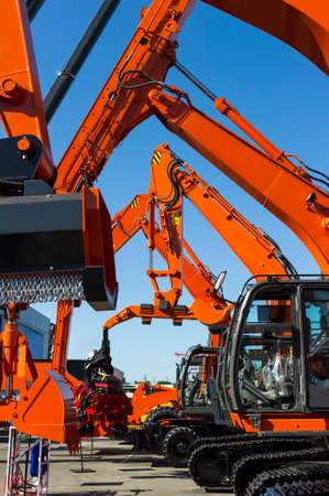 Bulldozer, excavator, tractor, front end loader and other orange construction machines with scoop, shovel, jackhammer and another equipment in row, heavy industry, blue on background Stock Photo