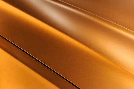specular: Surface of bronze sport sedan car metal hood, part of vehicle bodywork, steel gradient line pattern, selective focus