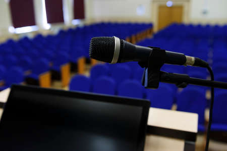 Microphone in conference hall, auditorium for business meeting and presentation with rostrum and display for speaker and rows of seats for participants and visitors on blurred background