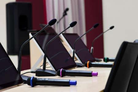 Konferenzraum für Business-Meeting, Tisch mit Mikrofonen, Displays und Stühlen für Teilnehmer in Zeile, selektiven Fokus