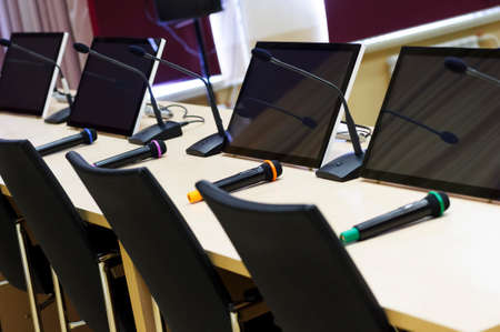 Conference room with microphones and displays on table and chairs for participants in row, business concept, before meeting, selective focus Lizenzfreie Bilder
