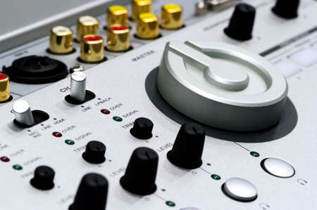 Detail of silver DJ mixer controller with buttons, switches, knobs, other toggle items, plugs and connectors, selective focus