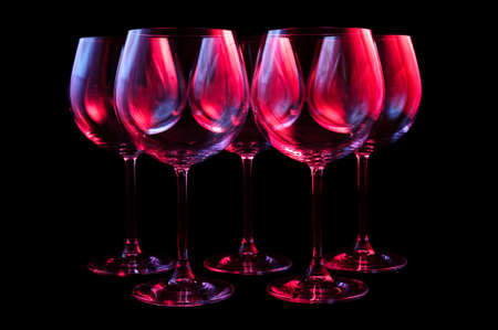 Nightclub wine glasses lit by red, blue, lilac party lights, nightlife, five object in row isolated on black background Lizenzfreie Bilder