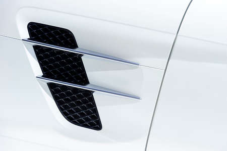 White sport car bodywork, metallic surface of a racing vehicle, concept of aerodynamic high speed transportation, detail of door, fender and air intake