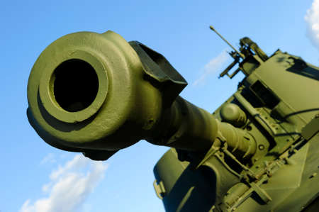 Cannon barrel of powerful green tank with blue sky on background, modern army artillery, military industry, selective focus Stock Photo