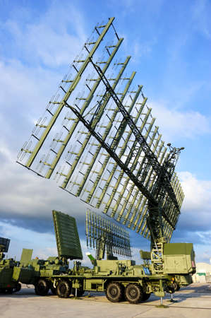 Air defense radars and locks of military mobile antiaircraft systems in green color, modern army industry, beautiful clouds and blue sky on background