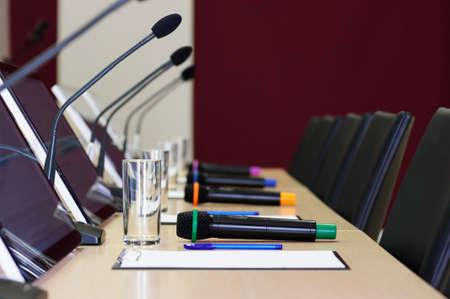 Conference room table for business meeting with microphones, monitors, pens, papers, glasses for water and chairs in row, selective focus Lizenzfreie Bilder