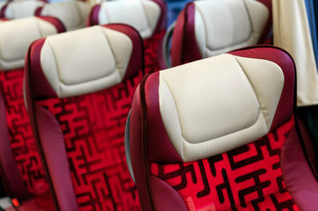 Bus seats in row with red leather, textile coating and white headrests, modern comfortable tourist transport interior, selective focus