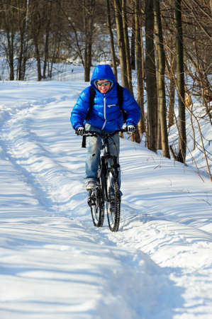 Extreme winter cyclist riding mountain bicycle with effort on rural track among snowbanks near snowy beautiful forest in sunny cold day Lizenzfreie Bilder