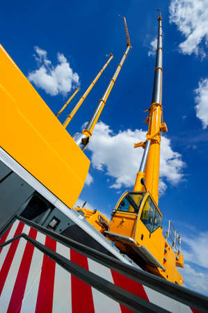 Mobile construction cranes with telescopic arms mounted on trucks with yellow bodyworks in sunny day with white clouds and deep blue sky on background, heavy industry Stock Photo