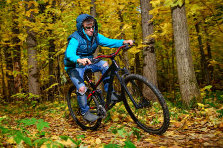 Cyclist extreme riding mountain bike on rural road in wild autumn colorful forest with impassable dried bushes