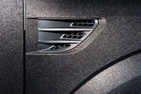 Surface of powerful black sub textured car bodywork, detail of vehicle side and fender with air vent
