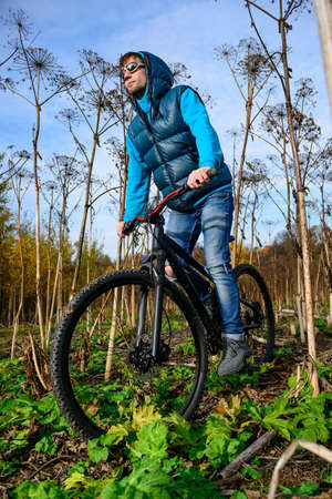 Cyclist extreme riding mountain bike through impassable dried bushes in wild autumn colorful forest