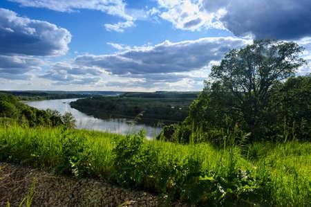 Ländliche Sommerlandschaft mit Fluss, Wald, grüne Felder, blauer Himmel und dramatische Wolken, Landschaft, hohe Winkelsicht, natürlicher Hintergrund
