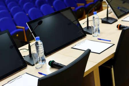 Konferenzsaal für Geschäftstreffen, Tisch mit Mikrofonen, Monitoren, Flaschen mit Wasser, Gläser, Papiere, Stifte und Stühle, blaue Sitze in Reihe auf unscharfen Hintergrund, selektiven Fokus