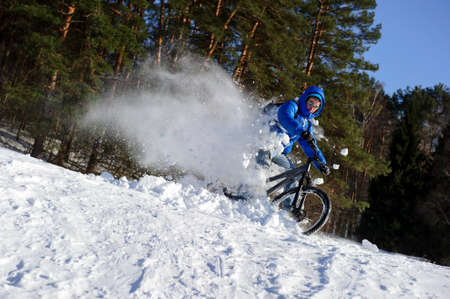 Cyclist extreme riding mountain bicycle in flying snow near winter forest in cold sunny day