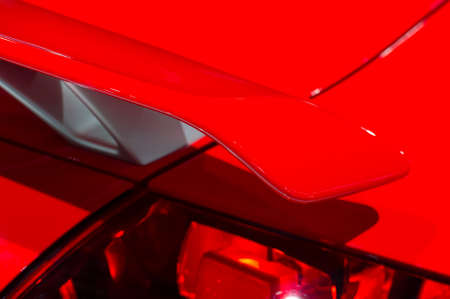 Curved spoiler of aggressive powerful sport car with red bodywork, selective focus Stock Photo