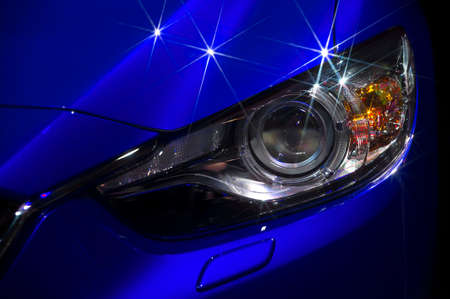 Headlight and hood of powerful sports blue car with stars on bodywork, isolated on black