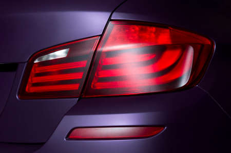 Car rear lights with a matte surface, red backlight of a lilac powerful sport sedan bodywork, concept