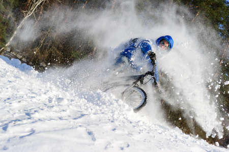 Extreme cyclist riding bicycle near snowbanks of mountain slope, winter sport, cross country biking near forest in sunny day