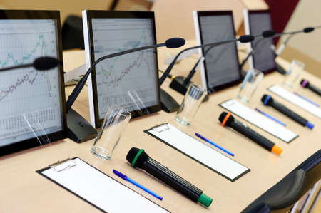 Conference room table for business meeting with microphones, monitors, pens, papers, glasses for water and chairs in row, selective focus Standard-Bild