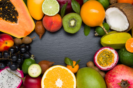 Exotic tropical fruits on black textured stone background, healthy food, vegetarian diet