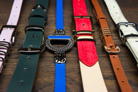 Womans leather belts in a row on a wooden background, accessories for ladies in classic, vintage and modern styles, fashion industry, selective focus